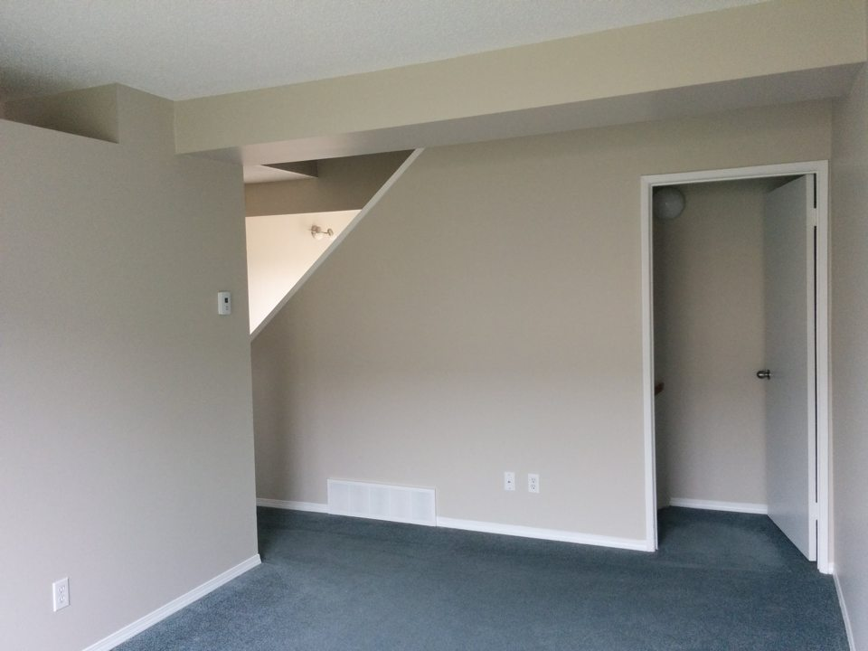 Two bedroom living room facing basement stairs